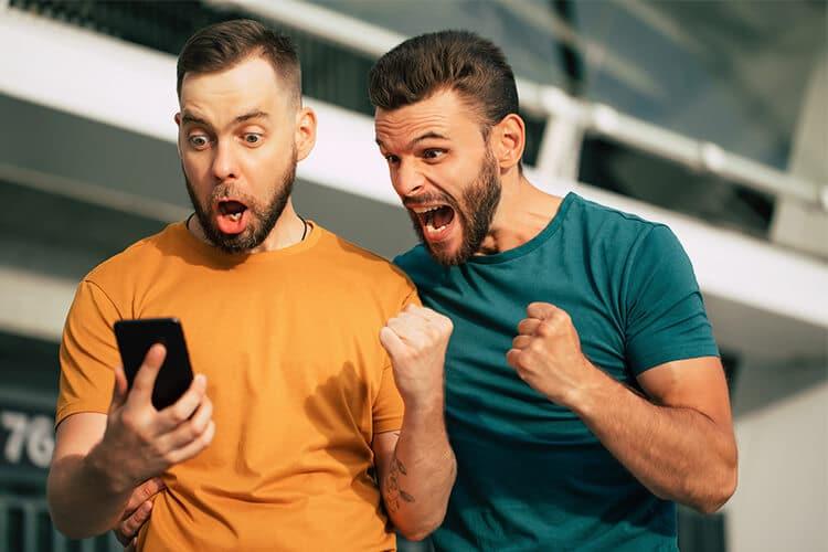 dos-hombres-con-un-celular-festejando-que-han-ganando-dinero-smartphone-teléfono-movil-buso-amarillo-buso-verde
