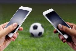 dos-personas-apostando-con-sus-smartphones-en-cada-mano-cancha-de-fútbol-pelota-de-fútbol