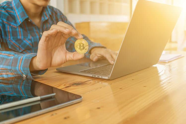 hombre-apostando-online-en-casas-de-apuestas-con-bitcoins-desde-su-computadora-camisa-a-cuadros-computadora-tablet-moneda-de-bitcoins