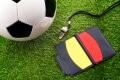 pelota-de-fútbol-sobre-el-pasto-con-un-silbato-de-árbitro-y-las-tarjetas-amarillas-y-rojas
