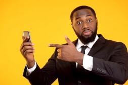 persona-de-traje-señalando-con-el-dedo-su-celular-para-mostrar-las-casas-de-apuestas