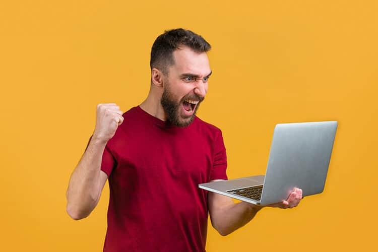 persona-que-ganando-dinero-en-te-apuesto-online-desde-su-computadora-remera-roja-puño-en-alto-festejando-