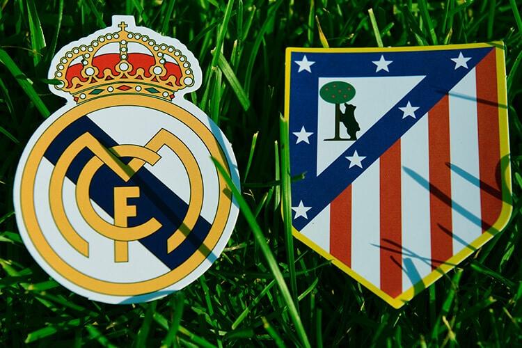 stickers-de-escudos-del-real-madrid-y-atlético-madrid-sobre-el-pasto-escudo-de-real-madrid-escudo-de-atlético-de-madrid-pasto-bien-verde-Betsson