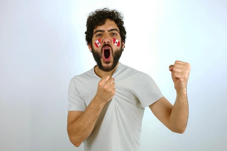 hombre festejando luego de apostar en te apuesto con la bandera de perú pintada en sus mejillas