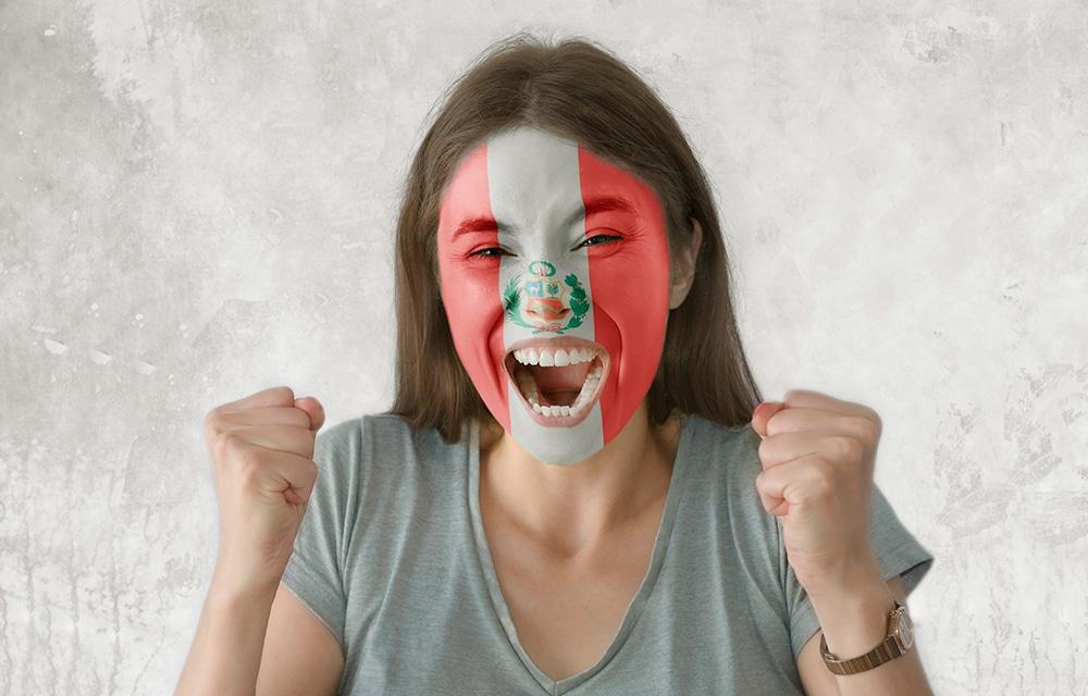 mujer festejando un gol de perú con la bandera de perú pintada en la cara