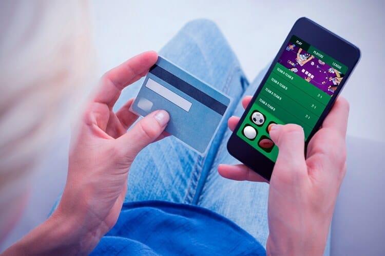 casas-de-apuestas-peru perona apostando desde su celular con la tarjeta de crédito en la mano izquierda