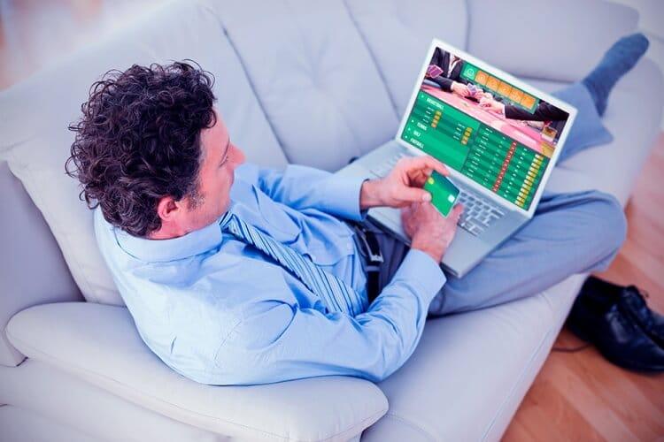 casas-de-apuestas-peru hombre sentado en un sillón vestido de traje mirando las casas de apuestas perú en su computadora