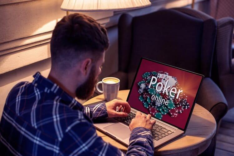 casas-de-apuestas-peru hombre apostando poker online desde la comodidad de su casa tomando un café